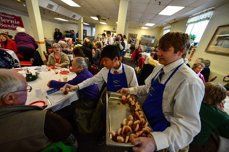 KRISTOPHER RADDER - BRATTLEBORO REFORMER<br /> McKade Beattie and Donavin Hamilton hand out shrimp cocktails during a Seniors Holiday Dinner that was sponsored by U.S. Senator Bernie Sanders on Thursday, Dec. 15, 2016.