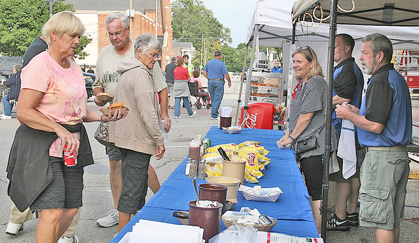 "BACK TO THE FIFTIES KICKS OFF<br /> Elizabeth Pearl | The Lebanon Reporter<br /> POODLING AROUND: People flocked around the Lebanon Elks Lodge booth for pulled pork sandwiches at the Back to the Fifties Festival on Friday evening on Lebanon's Courthouse Square. The event continues tomorrow from 9 a.m. to 4:30 p.m. with a Classic Car show, art and photography show, crafts, concerts and a magician, as well as an inflatable area for kids. For more information on today's schedule go online to  <a href=""http://www.fiftiesfestival.com"">http://www.fiftiesfestival.com</a>."