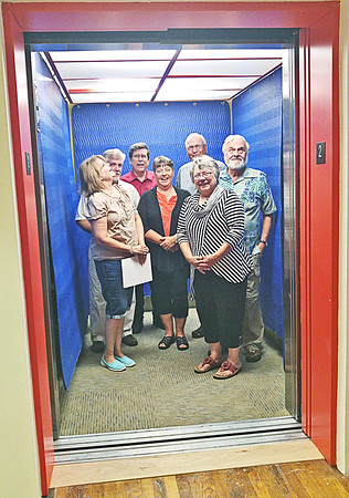 UP AND AWAY<br /> Elizabeth Pearl | The Lebanon Reporter<br /> READY FOR LIFTOFF: Volunteers, board members and guests at the Sugar Creek Art Center prepare to take a ride on the newly installed elevator on Friday. The center has been raising money for three years to get a new elevator installed, said Karen Wright (second from right), president of the Sugar Creek Art Center board. The state deemed the old freight elevator inadequate for use in 2013. Since then, the center has raised $150,000 for the installation of the new elevator and cut costs in order to help pay for it. <br /> The organization saved the wooden racks that lined the old elevator, Wright said. She hopes that in the future artists will incorporate them into their work.