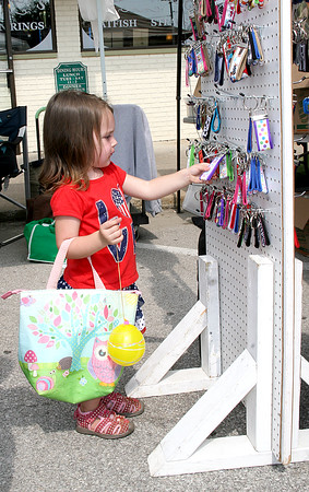 Rod Rose The Lebanon Reporter<br /> DECISIONS, DECISIONS: Kinley Bivens, 2, sorts through keychains at a booth on Main Street during Saturday's Festival of The Turning Leaves in Thorntown. A large crowd turned out to enjoy a parade, performances and games, and select from food, apparel, craft and other merchandise.