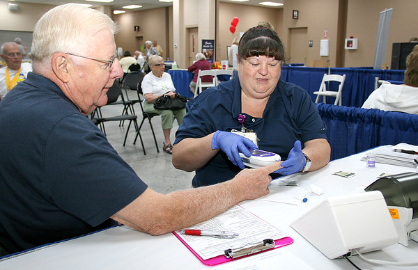 Rod Rose The Lebanon Reporter<br /> TESTING, TESTING: Leo Hamke of Lebanon holds steady as Witham Health Services emergency room nurse Tracy Hatfield takes a sample to measure his blood sugar, during Saturday's Boone County Senior Expo at the Boone County 4-H Fairgrounds.