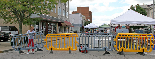 Rod Rose The Lebanon Reporter<br /> MARKET BARRICADE: Kelly Cook slots a section of barricade back into place after sliding it aside  Friday afternoon  so one of the vendors at Lebanon's Farmer's Market can move a vehicle. A supply of the lightweight yellow and gray barricades were recently purchased by the city.
