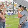 CLOUDY WITH A CHANCE OF BEER<br /> Elizabeth Pearl | The Lebanon Reporter<br /> PERFECTLY BREWED: Whitestown residents Erin Baumis (left) and Kelsey Oswalt enjoyed a beer tasting Saturday afternoon at the Whitestown Brew Fest despite a brief spattering of rain. Forty-five breweries participated in the second annual festival, held in the parking lot of the Whitestown Municipal Building from 1 p.m. to 5 p.m. Breweries from as far as Columbus and Bloomington, and as near as Noble Order Brewing in Zionsville passed out samples of their beers.