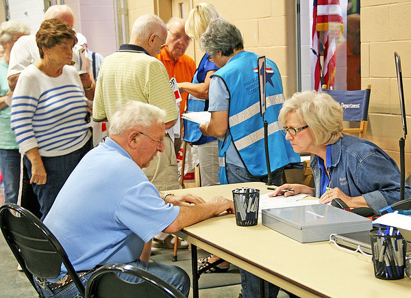 Rod Rose The Lebanon Reporter<br /> PRECAUTIONARY PREP: Leon Brandenburg files out forms with Judi Christenson of the Boone County Health Department before he receives an influenza and a  pneumonia vaccine at Saturday's Boone County Senior Expo at the Boone County 4-H Fairgrounds.