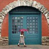 BEN GARVER — THE BERKSHIRE EAGLE<br /> A woman walks past the old firehouse (now the home of 1Berkshire)  in Pittsfield, Mass., Wednesday, September 12, 2018. The Northeast has has had several days of wet weather that is forecast to break by the weekend. (Ben Garver / The Berkshire Eagle via AP)