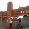 BEN GARVER — THE BERKSHIRE EAGLE<br /> Two women walk past the old firehouse (now the home of 1Berkshire)  in Pittsfield, Mass., Wednesday, September 12, 2018. The Northeast has has had several days of wet weather that is forecast to break by the weekend. (Ben Garver / The Berkshire Eagle via AP)