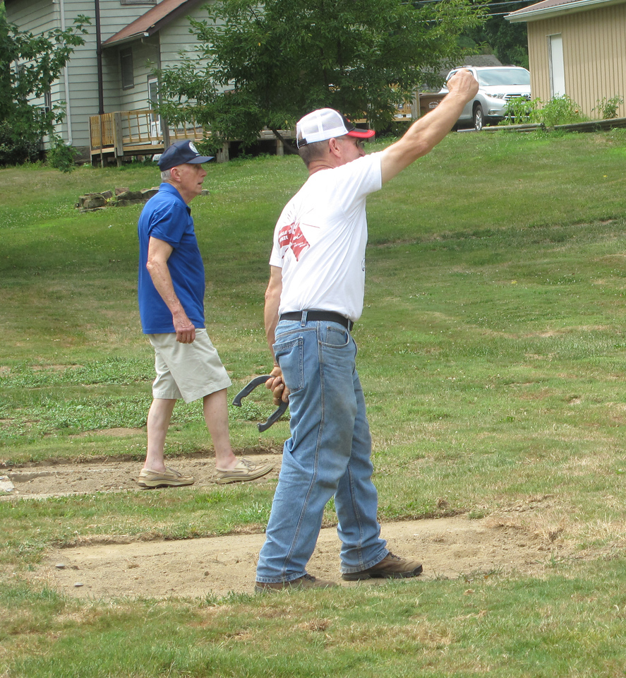 ELIZABETH DOBBINS / GAZETTE Seville resident Paul Oberli, 79, left, plays a game of horseshoes with 60-year-old Carl Perry, also of Seville, during the Village of Seville Bicentennial Celebration.