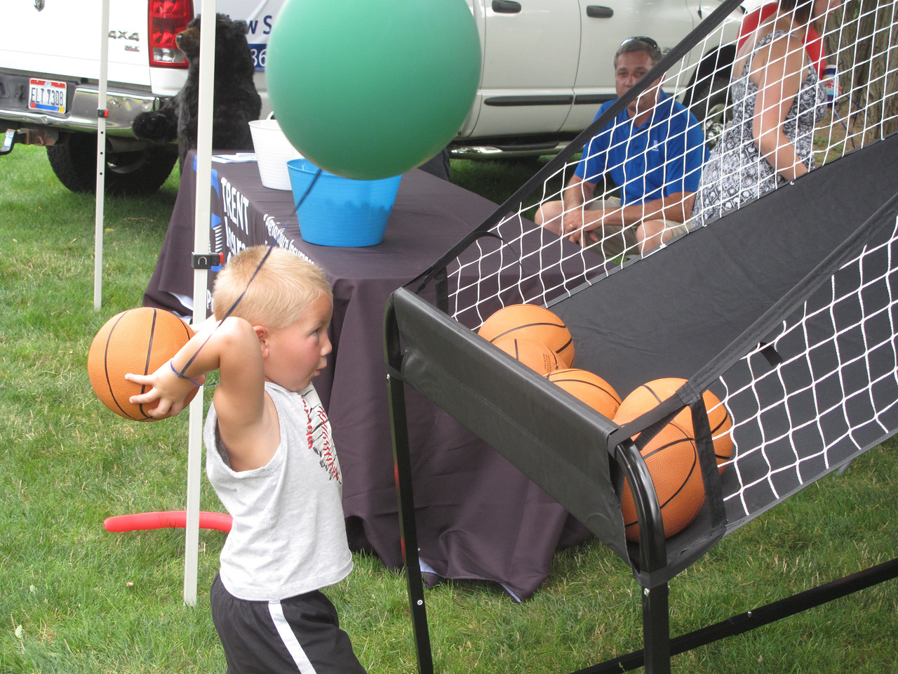ELIZABETH DOBBINS / GAZETTE Jaxson Musser, 4, of Sterling Township, tests his basketball at the Village of Seville Bicentennial Celebration Sunday afternoon.
