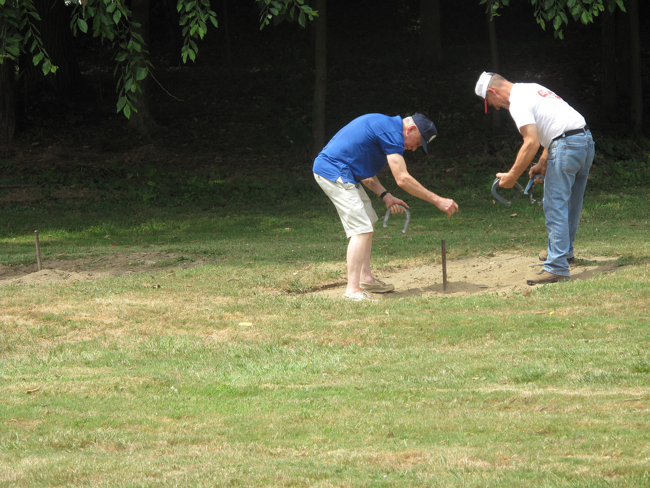 072516seville05 ELIZABETH DOBBINS / GAZETTE Seville resident Paul Oberli, 79, left, plays a game of horseshoes with 60-year-old Carl Perry, also of Seville, Village of Seville Bicentennial Celebration.