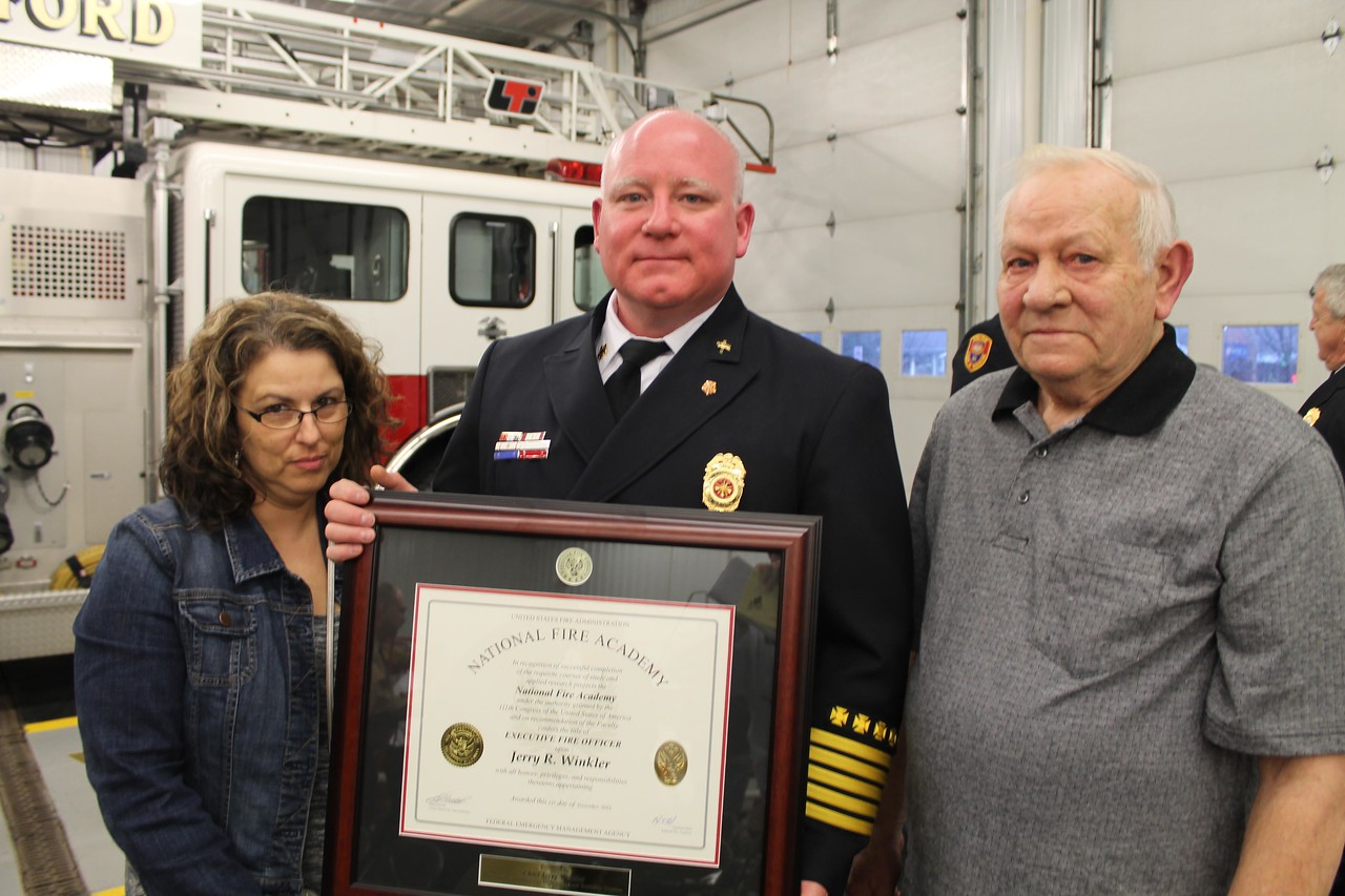 LAWRENCE PANTAGES / GAZETTE Seville Fire Chief Jerry Winkler was joined by his wife Anita and father Delbert for a ceremony Thursday at the station commemorating his completion of a National Fire Academy certification as an EFO, or Executive Fire Officer. The program required two weeks of training and education each year for four years and four research assignments.