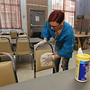 Employees at the Lowell Transitional Living Center are regularly cleaning and disinfecting surfaces to reduce the risk of COVID-19. Case manager Carla Bettencourt cleans the dining room chairs and tables, which is done after every meal and meeting. (SUN/Julia Malakie)