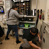 Employees at the Lowell Transitional Living Center are regularly cleaning and disinfecting surfaces to reduce the risk of COVID-19. Program advocate Beronica  Paulino, left, and case manager Tony Marrero, right, wipe surfaces with bleach wipes. (SUN/Julia Malakie)