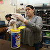 Employees at the Lowell Transitional Living Center are regularly cleaning and disinfecting surfaces to reduce the risk of COVID-19. Program advocate Beronica  Paulino wipes surfaces at the reception desk with bleach wipes.  At rear is case manager Yaritza Scarpatte. (SUN/Julia Malakie)