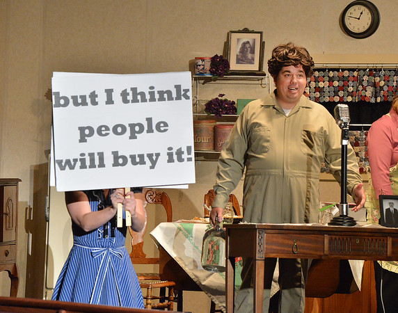 Elizabeth Huddle, left, playing Nadine, holds up a sign for the audience as Matt Martin, playing Emmett McElroy, announces another invention during Saturday's performance of Hometown Memories a Shepard of Love Fellowship melodrama dinner theater production .<br /> August 11, 2012<br /> staff photo/ David R. Jennings