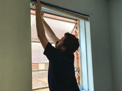 ALYSSA ALFANO / GAZETTE Sherwin-Williams employee Joe Vidmar paint arounds a window in the guidance counselor's office at Evolve Academy on Thursday as part of a volunteer partnership with the school.