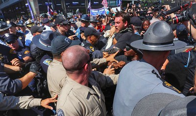 Police officers fight with the crowd as they try to make arrests at East 4th and Prospect. BRUCE BISHOP/GAZETTE