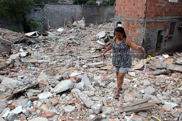 Francileide da Costa Souza, 42 walks through rubble in the Mangueira Metro slum, near the Maracana Stadium in Rio de Janeiro, Brazil. Residents say they are being evicted, and their homes destroyed, to make way for a possible parking area for the stadium, which will host the World Cup in 2014 and the Olympics in 2016. (Australfoto/Douglas Engle)
