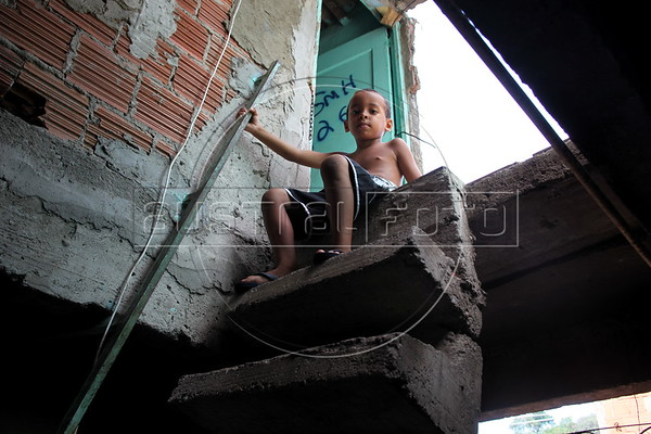 A boy sits in his home in the Mangueira Metro slum, near the Maracana Stadium in Rio de Janeiro, Brazil. Residents say they are being evicted, and their homes destroyed, to make way for a possible parking area for the stadium, which will host the World Cup in 2014 and the Olympics in 2016. (Australfoto/Douglas Engle)