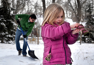 Boulder resident Oliver McBryan, left, 30, shovels the snow as his daughter Scarlet McBryan, 4, takes a break to put on her gloves, in  Boulder on Tuesday Jan. 29, 2013. DAILY CAMERA/ JESSICA CUNEO.