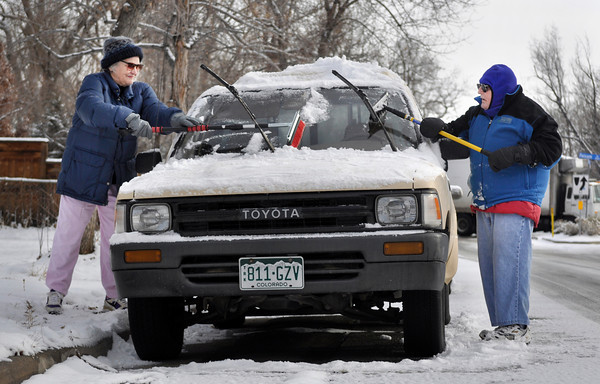 Boulder residents Marion Gately, left, and her husband Richard Gately scrape off snow on Marion's truck in  Boulder on Tuesday Jan. 29, 2013. DAILY CAMERA/ JESSICA CUNEO.