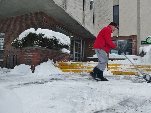 JENN SMITH — THE BEKRSHIRE EAGLE <br /> Steve Gavazzi of A1 Incorporated shovels snow to clear sidewalks outside some Main Street businesses in North Adams on Monday. Monday, December 2 2019