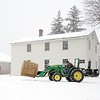 BEN GARVER — THE BERKSHIRE EAGLE<br /> Russell Sorrell moves a bail of hay from storage, past the workers living quarters to the barn at Hancock Shaker Village, Tuesday, April 13, 2018.