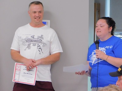 BOB FINNAN / GAZETTE Dan Moomey gets a certificate in track from his coach at the Medina County Board of Developmental Disabilities' spring sports banquet at Veterans Memorial Hall in Medina on Tuesday.