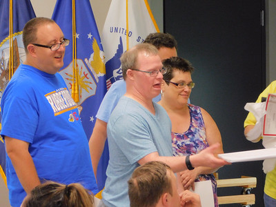BOB FINNAN / GAZETTE A bowler gets a certificate for his performance at the state tournament and congratulations from his teammates Tuesday at the Medina County Board of Developmental Disabilities' spring sports banquet at Veterans Memorial Hall in Medina.