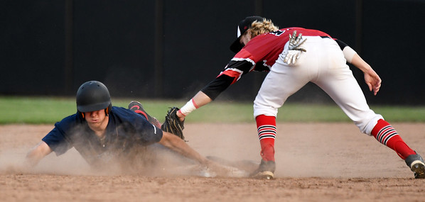 Outlaws shortstop Jeff Wetzler applies a late tag to Ozark's Ryan Curtis during Joplin's home opener on Friday night at Joe Becker Stadium.<br /> Globe | Laurie Sisk