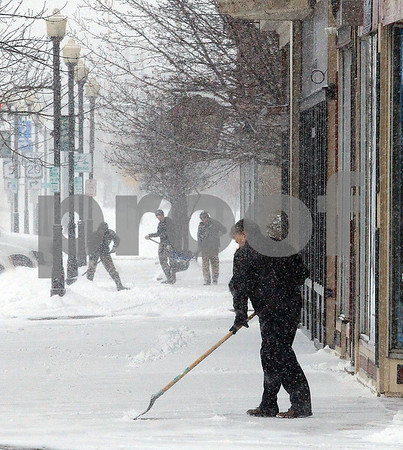 Spencer Tulis/Finger Lakes Times Jim Greco, foreground, shovels the sidealk in front of Lake Street Hobby in Geneva Tuesday as the winter storm Stella started her arrival.