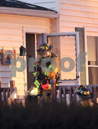 Spencer Tulis/Finger Lakes Times A firefighter rescues a dog from a structure fire on Inslee Street in the village of Waterloo Wednesday. Several fire companies responded to the fire where the residential home sustained considerable damage.