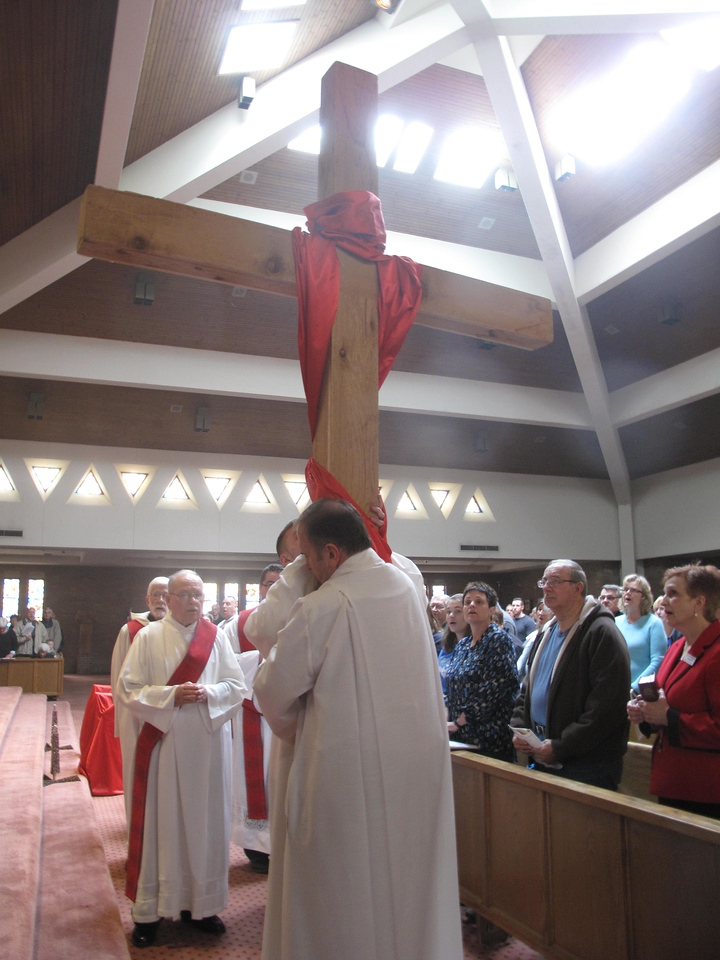ELIZABETH DOBBINS / GAZETTE Rev. Bob Stec lifts the cross as a procession brings the cross into the parish.