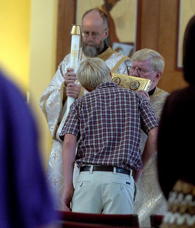 "Peter Knutsen kisses the Gospel held by Rev. Fr. David Mustian at the Sunday service of the St. Luke Christian Church.<br /> For more photos of the church, go to  <a href=""http://www.dailycamera.com"">http://www.dailycamera.com</a>.<br /> Cliff Grassmick / September 5, 2010"