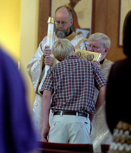 Peter Knutsen kisses the Gospel held by Rev. Fr. David Mustian at the Sunday service of the St. Luke Christian Church. For more photos of the church, go to www.dailycamera.com. Cliff Grassmick / September 5, 2010