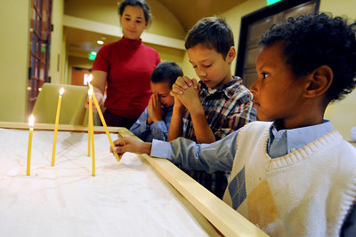 Kiah Boyd, left, her brothers, Donovan, Ian and Micah, light candles and pray before the Sunday  service at St Luke Orthodox Christian Church in Erie. For more photos of the church, go to www.dailycamera.com. Cliff Grassmick / September 5, 2010