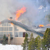 Walt Hester | Trail Gazette<br /> Flame erupt from the main lodge building on Monday at the St. Malo Retreat Center south of Estes Park. Firefighters from Estes Park, Allenspark and Big Elk Meadows rushed to the fire on Monday morning.