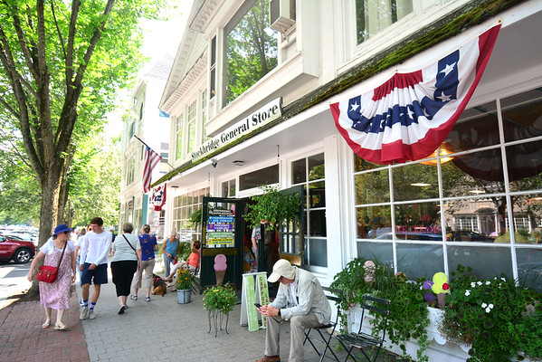 GILLIAN JONES — THE BERKSHIRE EAGLE<br /> Visitors walk past and gather at the Stockbridge General Store on Monday. The town of Stockbridge is forming a task force to explore ways to diversify its economy beyond hospitality.