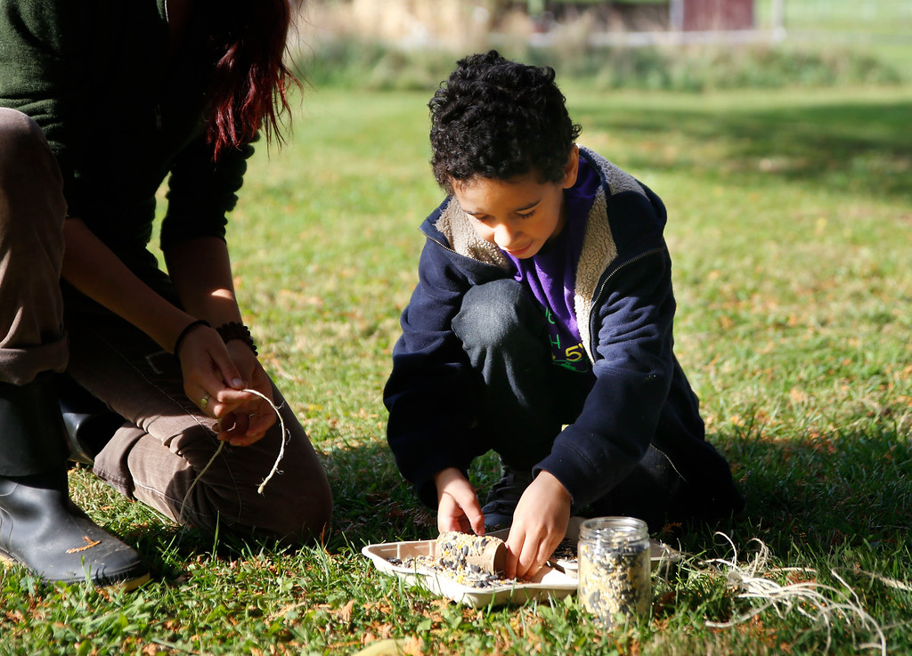 . Kylel West rolls a toilet paper roll in penut butter and seeds to feed the birds during the Autumn season.