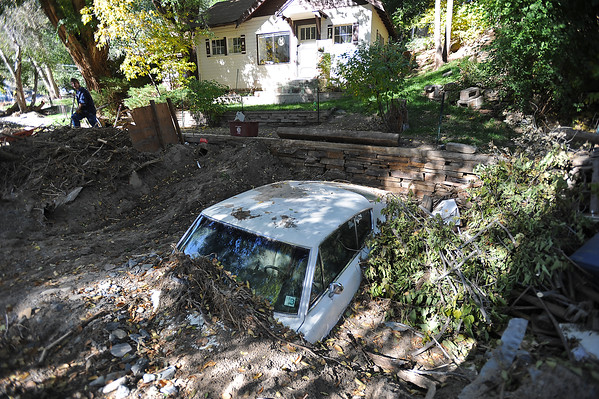 Carrie Hayes, left, works Wednesday, October 23, 2013, shoveling mud and silt away from her home on Hummingbird Lane west of Loveland. A 1969 Barracuda, her first car, sits buried in the mud in front of her home. (Photo by Jenny Sparks/Loveland Reporter-Herald)