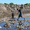 Henry Laviolette, right, and his son Elijah, 4, explore an area Tuesday, October 1, 2013, near Namaqua Road where flood waters left a ravine more than 7 feet deep.  Namaqua Road re-opened Tuesday after being closed since the flood. (Photo by Jenny Sparks/Loveland Reporter-Herald)