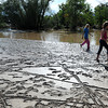 Quinn Doyle, 5, left, and his sisters, Sofie, 11, center right, and Abby, 10, far right, walk through mud left behind by the flood on Taft Avenue north of First Street in Lovelandon Friday, Sept. 13.