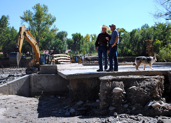 Standing on the bridge over the Big Thompson river where the road was washed away by flood waters, David Jessup, owner of Sylvan Dale Guest Ranch, talks with a man surveying damage Thursday, September 26, 2013 in west Loveland. The guest ranch sustained heavy damage in the Front Range flood. (Photo by Lilia Munoz/Loveland Reporter-Herald)