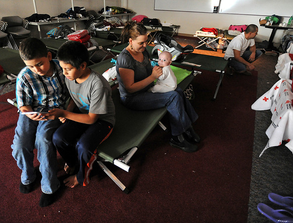 "Flood evacuee Daisy Velasco plays with her baby Caleb Bernal, 4 months, as her nephew Joan Favela, 11, left, and Jesus Jimenez, 12, play a video game at the Red Cross Shelter in Loveland Friday, September 13, 2013. Velasco said ""Not being home"" has been difficult. (Photo by Jenny Sparks/Loveland Reporter-Herald)"