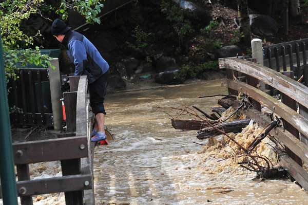 18EP Flood 2 Bad Bridge.jpg A  reckless young man slides over the bridge at Trejent Park on Friday. Large amounts of debris colecting on the bridge could have led to the bridge's failure, but not this time.