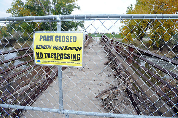 A sign seen on one of the bridges that link Fairgounds Park and Barnes Park seen Thursday, October 17, 2013, warn folks of the flood damage. (Photo by Jenny Sparks/Loveland Reporter-Herald)