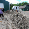 Diana Carnahan, right, and her husband Ken stand surrounded by mud left behind from the flood near their workshop and barn at their Glade Road home Monday, September 16, 2013. (Photo by Jenny Sparks/Loveland Reporter-Herald)