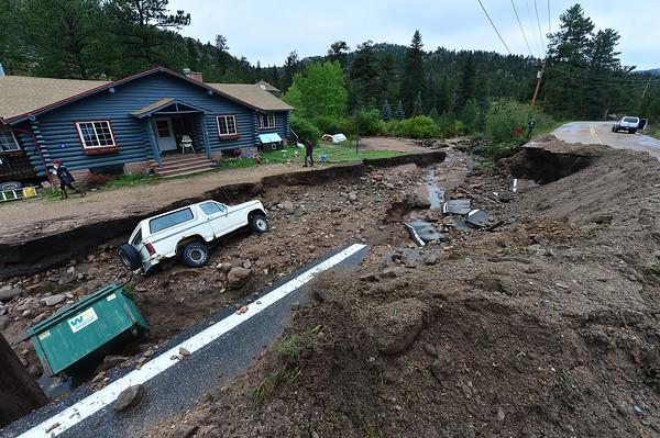 17EP Flood Glen Haven Road.jpg A dumpster and an SUV rest in a gully above Glen Haven formed by last week's flood. Roads, property and lives were lost in the single largest flood event in the state's history.