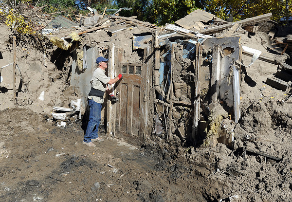 Val Strals knocks on the front door of his flood ravaged home as he jokes with volunteers, not pictured, as they try to salvage some belongings from his home on Hummigbird Lane west of Loveland on Wednesday, October 23, 2013. Strals' home was completely covered with silt and mud from the flood so he dug into it to see what he could salvage. (Photo by Jenny Sparks/Loveland Reporter-Herald)
