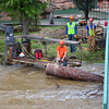17ep flood big thompson chainsaw.jpg A worker uses a chainsaw to break up a tree lodged under a foot bridge over the Big Thompson River Monday morning in Estes Park. The cleanup effort has begun now that the rains have stoped and the water is receeding.