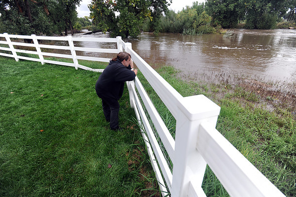Alicia Rowley looks Thursday, September 12, 2013, at the much closer waterfront view of the Big Thompson River behind the Waterford Place Apartments in Loveland as the river floods the area. Residents of the complex were evacuated. (Photo by Jenny Sparks/Loveland Reporter-Herald)